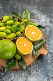 Close-up lateral de frutas cítricas frutas cítricas com folhas na placa de madeira