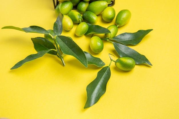 Close-up lateral de frutas cítricas frutas cítricas com folhas no centro da mesa