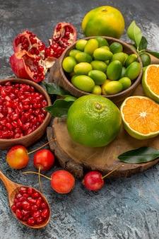 Close-up lateral de frutas cítricas sementes de romã em uma tigela cerejas frutas cítricas no quadro
