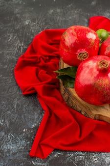 Close-up lateral de frutas com romãs maduras na placa de madeira sobre a toalha de mesa vermelha