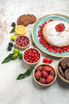 Close-up lateral de frutas e biscoitos, o bolo com morangos, biscoitos de limão e frutas cítricas