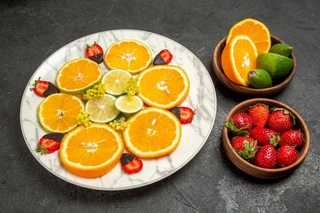 Close-up lateral de frutas em pratos de mesa com frutas cítricas e bagas ao lado do prato de morangos com cobertura de chocolate e frutas cítricas na mesa