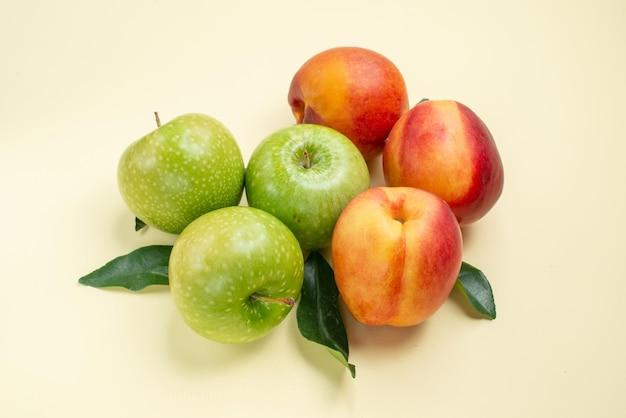 Close-up lateral de maçãs e nectarinas, três nectarinas e três maçãs com folhas verdes