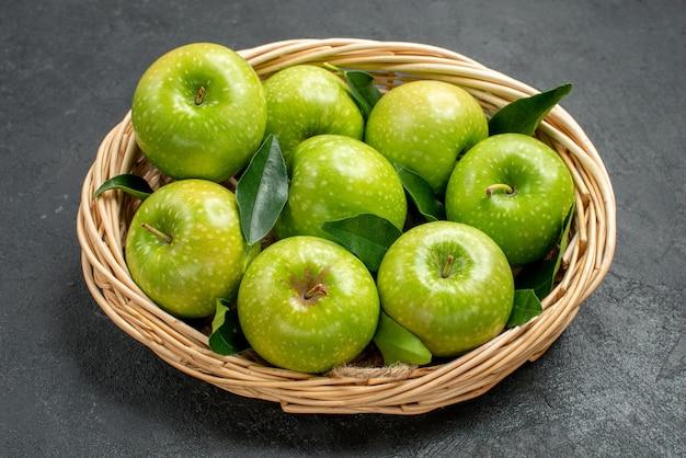 Close-up lateral de maçãs em uma cesta de madeira com oito maçãs com folhas na mesa escura