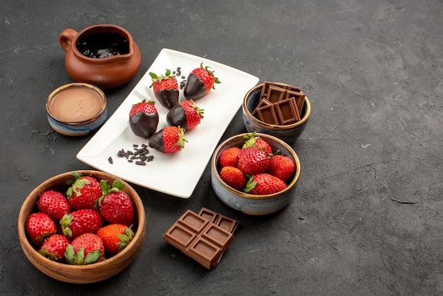 Close-up lateral de morangos creme de chocolate prato branco de morangos cobertos de chocolate, barras de chocolate e creme de chocolate em uma tigela na mesa escura