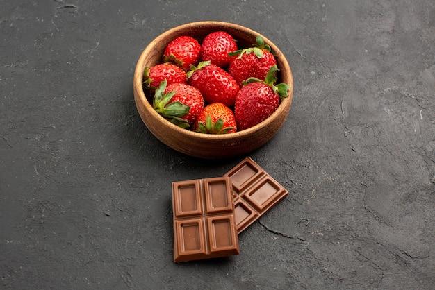 Close-up lateral de morangos em uma tigela com barras de chocolate ao lado dos morangos em uma tigela na mesa escura