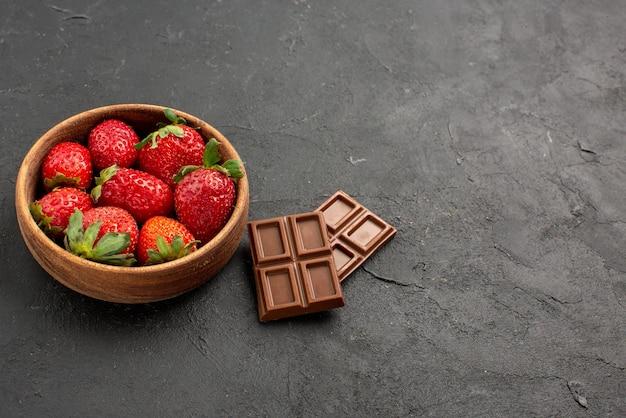 Close-up lateral de morangos em uma tigela morangos em uma tigela ao lado de barras de chocolate na mesa escura
