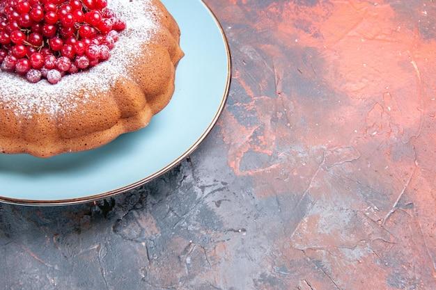 Close-up lateral de um bolo apetitoso um bolo e frutas no prato azul