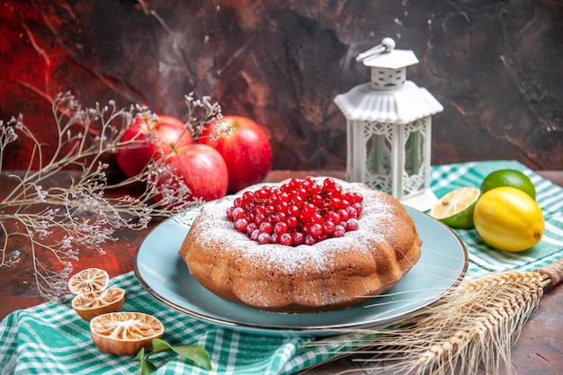 Close-up lateral de um bolo um bolo apetitoso com frutas cítricas na toalha de mesa maçãs