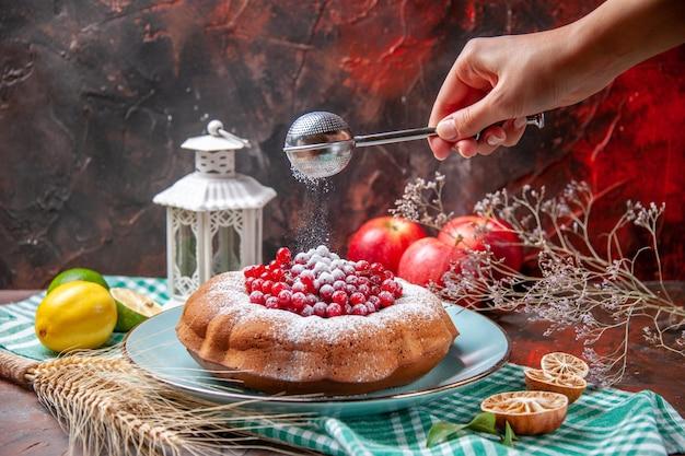 Close-up lateral de um bolo um bolo com frutas cítricas maçãs colher na mão