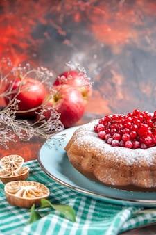 Close-up lateral de um bolo um bolo com frutas vermelhas na toalha de mesa quadriculada três galhos de maçãs