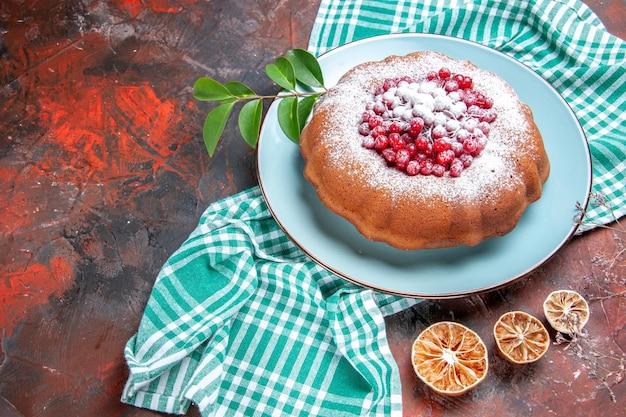 Close-up lateral de um bolo um bolo com groselha e açúcar de confeiteiro na toalha de mesa de limão