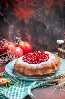 Close-up lateral de um bolo um bolo com groselha na toalha de mesa três maçãs espigas de trigo