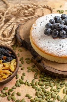 Close-up lateral de um bolo um bolo com uvas pretas sementes de abóbora corda passas na tigela