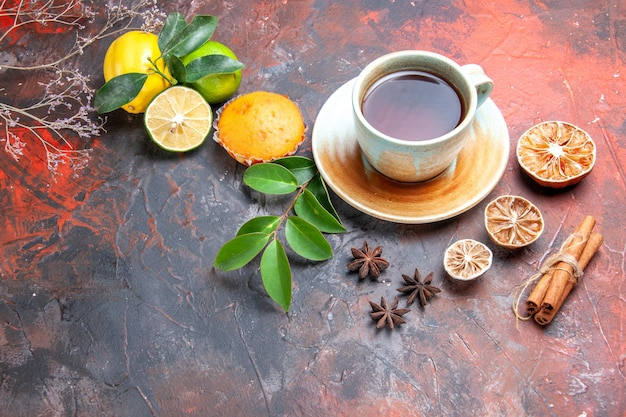 Close-up lateral de uma xícara de chá com creme xícara de chá preto, limão, anis estrelado, cupcake, canela