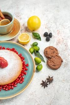 Close-up lateral do bolo apetitoso o bolo com frutas vermelhas uma xícara de chá com biscoitos de chocolate com limão anis estrelado na mesa