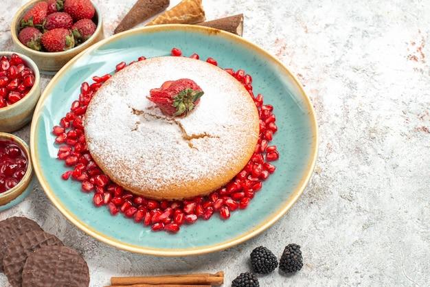 Close-up lateral do bolo bolo de paus de canela com biscoitos de frutas silvestres e diferentes frutas silvestres