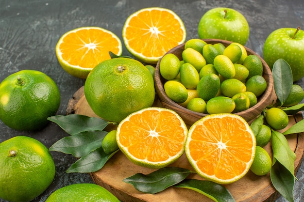 Close-up lateral frutas cítricas as frutas cítricas apetitosas na tábua de cortar maçãs verdes