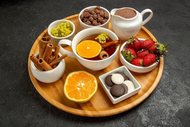 Close-up lateral uma xícara de chá com doces de chocolate creme uma xícara de chá limão, morangos, chocolate e castanhas no prato de madeira