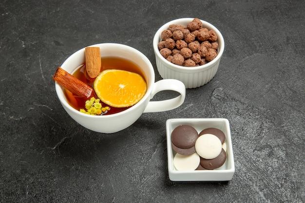 Close-up lateral uma xícara de chá de nozes uma xícara de chá com cinnabon e limão e tigelas de chocolate e nozes de nozes no fundo escuro