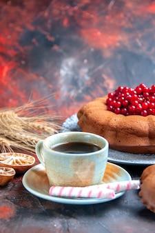 Close-up lateral uma xícara de chá um bolo apetitoso uma xícara de chá preto doces espigas de trigo