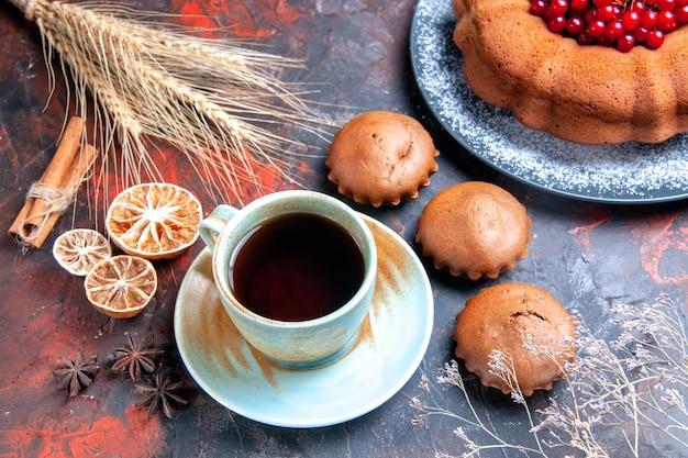 Close-up lateral uma xícara de chá uma xícara de chá com doces canela em pau prato de limão com bolo