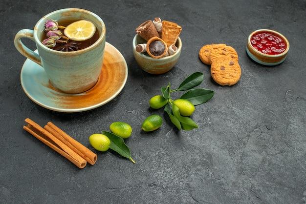 Close-up lateral uma xícara de chá uma xícara de chá com limão, canela, frutas cítricas, geleia de biscoitos
