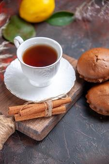 Close-up lateral uma xícara de cupcakes de chá uma xícara de chá canela frutas cítricas galhos de árvores