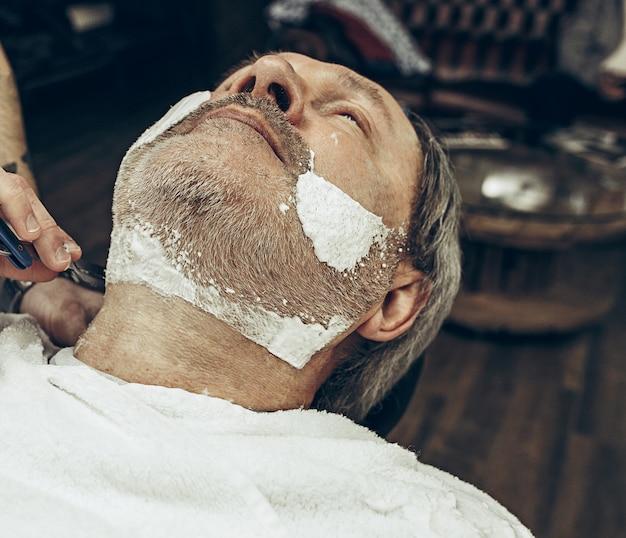 Close-up lateral vista superior bonito caucasiano barbudo homem ficando barba aliciamento na barbearia moderna.