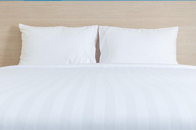 Close-up lençóis brancos e travesseiro no quarto de hotel