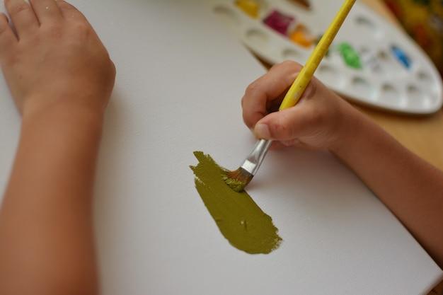 Close-up lettle child mãos pintura por painbrush e dor verde ao ole.