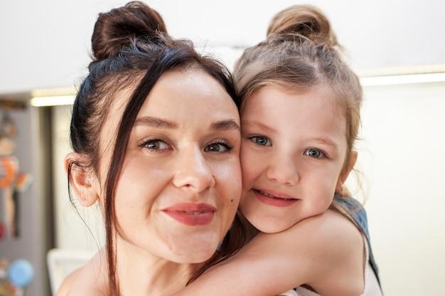 Close-up linda garota jovem abraçando a mãe