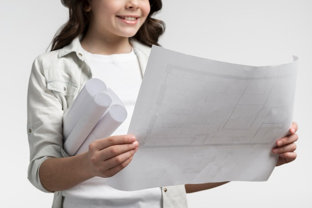 Close-up linda garota lendo plano de construção