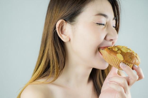 Close-up linda mulher asiática comendo um bolinho