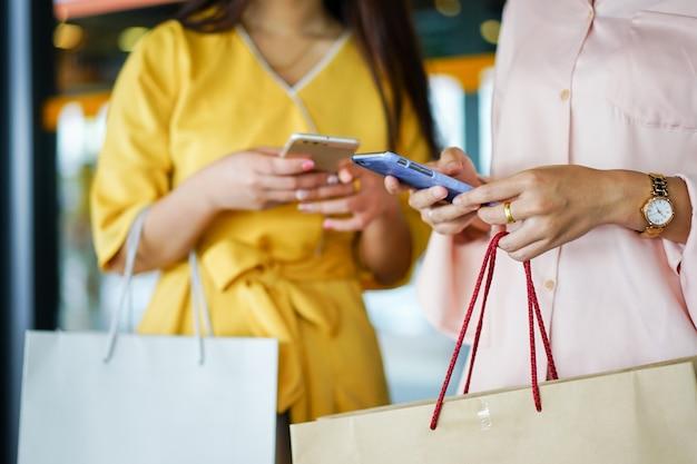 Close-up lindas mulheres asiáticas segurando o smartphone enquanto carregam sacos depois de terminar de fazer compras