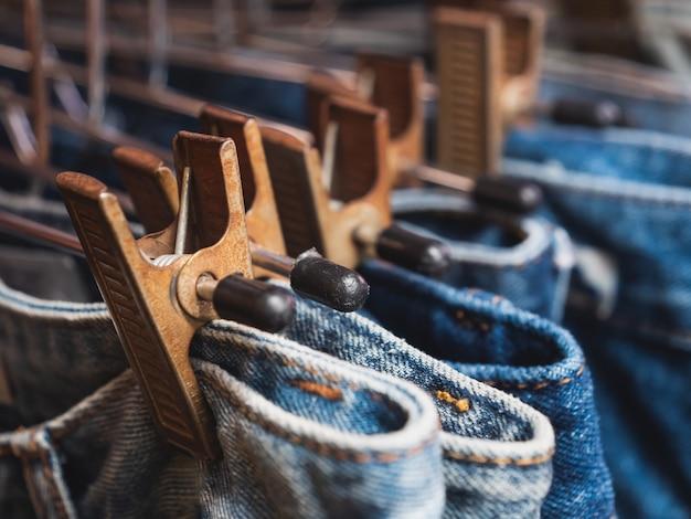 Close-up linha de muitas calças de ganga estão penduradas na loja