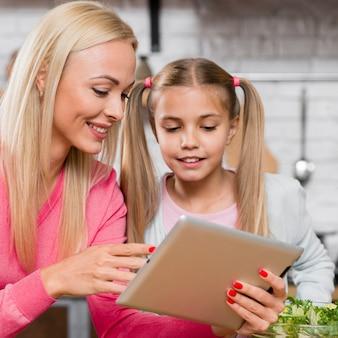 Close-up mãe e filha olhando para um tablet digital