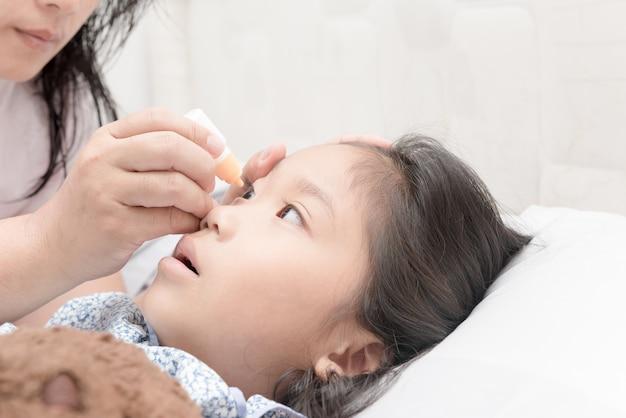Close-up mãe pinga nos olhos da menina uma solução medicinal, conceito de atendimento saudável