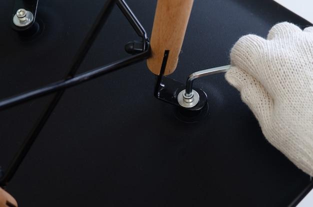 Close-up, mão de carpinteiro aparafusamento caminho de cadeiras com chave hexadecimal