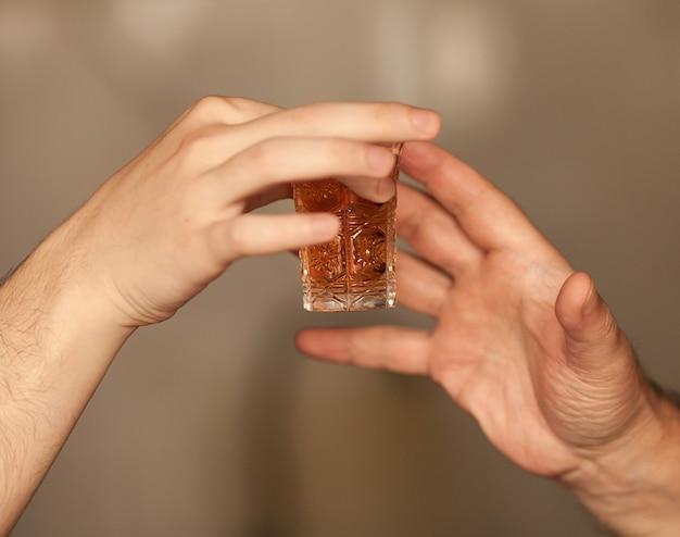 Close-up mão de homem toma um copo com álcool