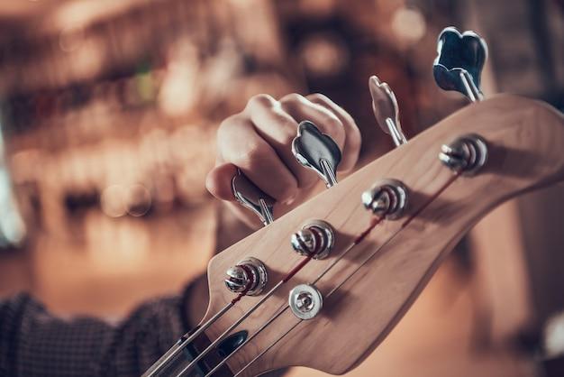 Close-up mão de homem torce pinos na guitarra fretboard