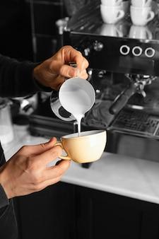 Close-up mão derramando leite no copo
