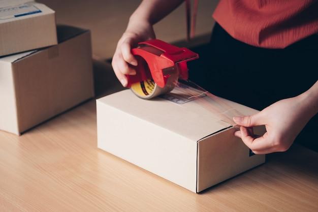 Close-up mão embalagem caixas de encomendas se preparar para entrega