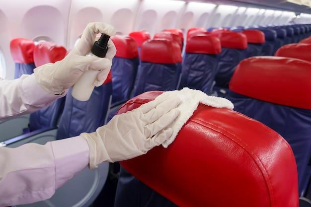 Close-up mão está usando luvas de limpeza de assento de avião para pandemia de prevenção covid-19