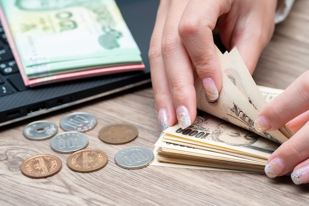 Close-up mão feminina contando notas de volta ienes japoneses