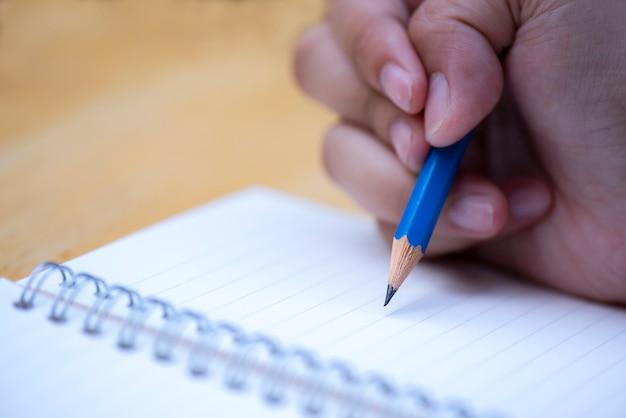 Close-up mão segurando a caneta escrevendo caderno em madeira fundo