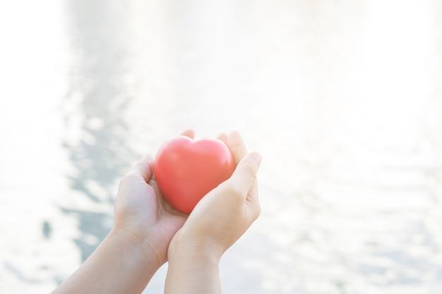 Close-up mão segurando coração vermelho no fundo do rio e a água macia