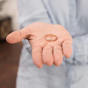Close-up mão segurando o anel de casamento