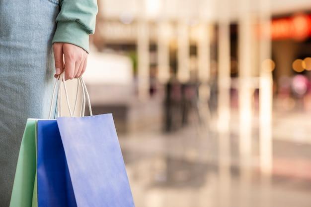 Close-up mão segurando sacolas de compras