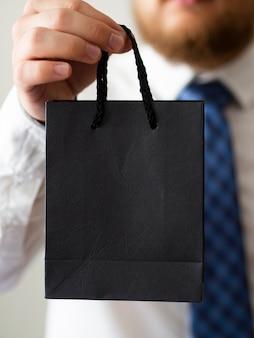 Close-up mão segurando um saco preto mock-up